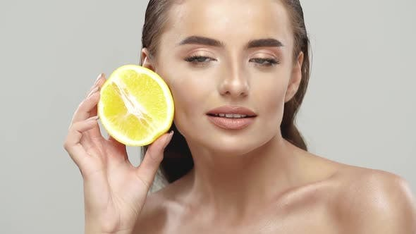Gorgeous Woman Holding Orange and Stroking Her Face