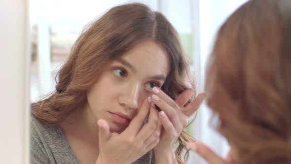 Thumbnail for Young Woman Removing Contact Lenses for Eyes at Mirror in Home Bathroom