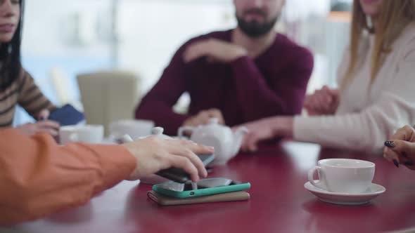 Thumbnail for Nahaufnahme der Gruppe von Unerkennbaren Menschen Putting Smartphones auf den Tisch im Café. Freunde
