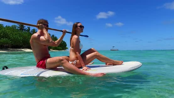 Beautiful man and woman in love dating on vacation spend quality time on beach on paradise white san