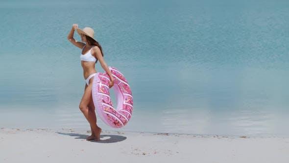 Женщина на пляже с резиновым кольцом