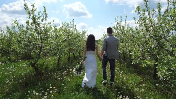Thumbnail for Happy Couple Walking Hand in Hand Among Trees