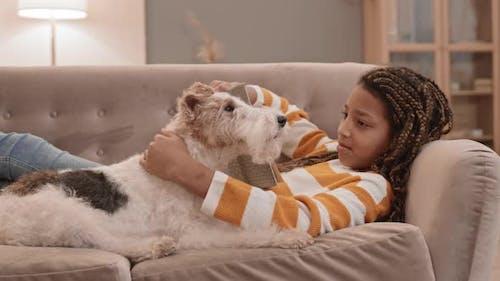 Mädchen und Hund auf Couch faulenzen