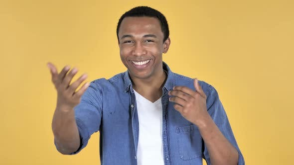 Thumbnail for Young African Man Inviting Customers with Both Hands, Yellow Background