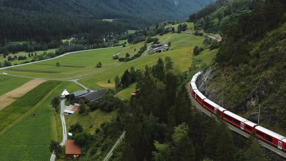 Thumbnail for Drone Tracking Famous Red Glacier Express Train Cruising Through Majestic Summer Switzerland Alps