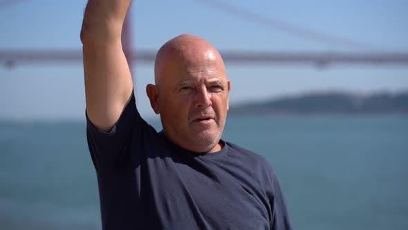 Thumbnail for Focused Bald Man Exercising at Riverside