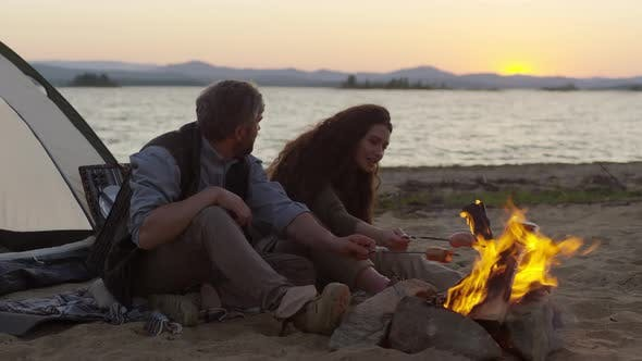 Thumbnail for Couple Cooking Sausages over Fire for Picnic on the Beach
