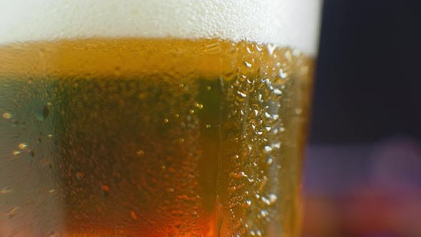Thumbnail for Macro Shot of a Drop Running Over a Glass of Beer. Sweat on a Cold Glass of Beer. A Dripping Drop on
