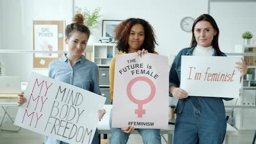 Slow Motion of Happy Feminists Standing with Posters Smiling Looking at Camera Indoors