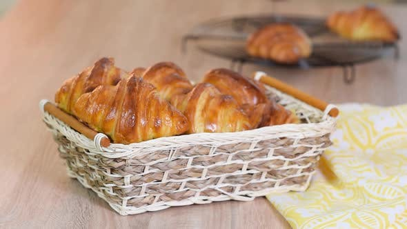 Fresh croissants in a basket on a wooden table