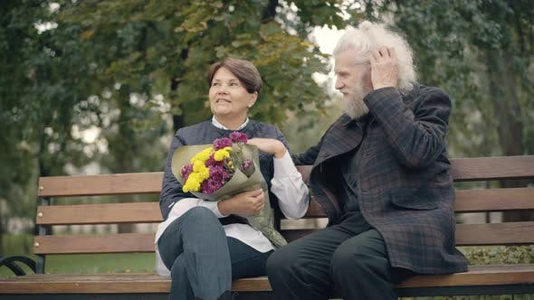 Positive Relaxed Couple of Caucasian Retirees Sitting on Bench in Autumn Park Talking