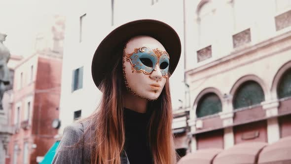 Thumbnail for Woman with Long Hair and Hat Wearing a White Carnival Face Mask in Venice Street, Italy Looking at