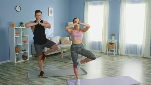 Man and Woman Practice Yoga Tree Pose and Have Fun at Home