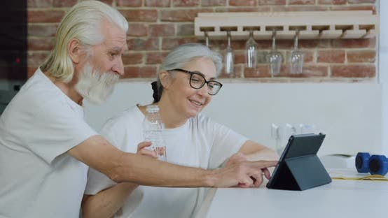 Old bearded Man and His Wife Sitting at Kitchen Table and Watching Interesting Videos