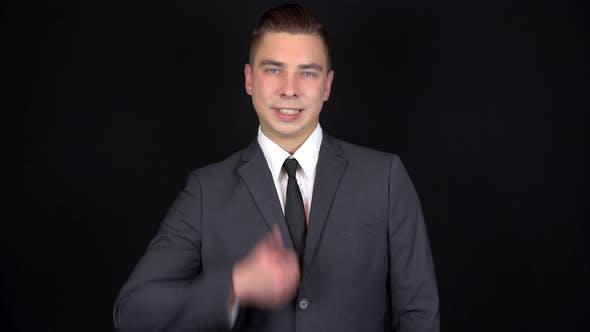 Thumbnail for Junge Geschäftsmann zeigt wie auf der Hand. Mann in einem schwarzen Anzug auf einem schwarzen Hintergrund
