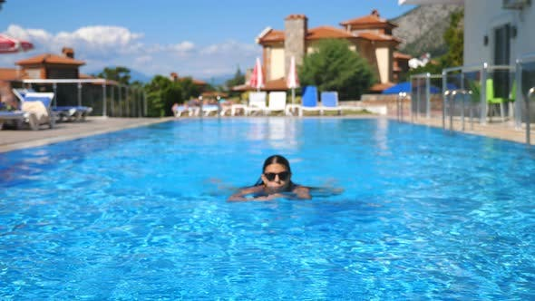 Thumbnail for Sexy Girl in Black Swimsuit Relaxing in Pool of Luxury Hotel. Lady Resting on Resort. Young Woman in