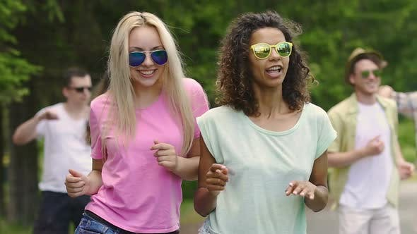 Thumbnail for Two Female Friends Dancing and Talking at Party in Park, Guys Enjoying Summer