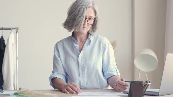 Senior Older Elegant Woman Fashion Designer Drawing Sketches on Table