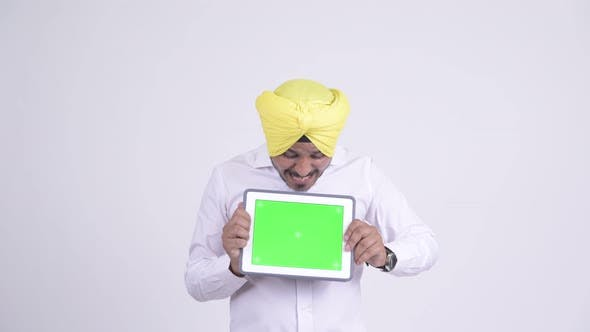 Thumbnail for Happy Indian Sikh Businessman Looking Surprised While Showing Digital Tablet