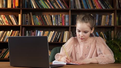 Young Lady Looks at Laptop Screen and Writes in Copybook