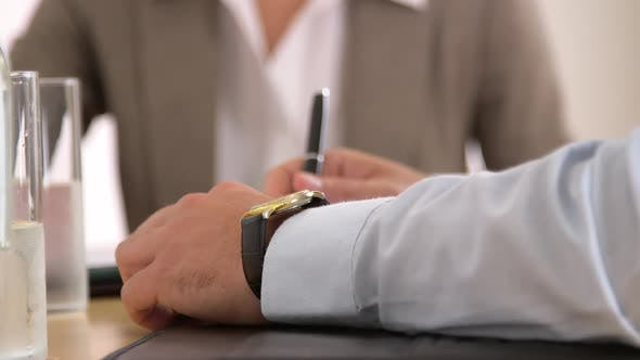 Thumbnail for Businessman checking his watch in a meeting