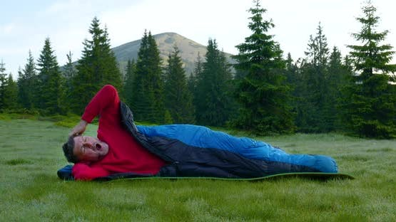 Bearded Man Sleeping in a Sleeping Bag on a Beautiful Meadow in the Mountains