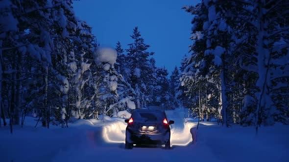 Nacht Schneefall im Winterwald und ein Auto mit Scheinwerfer