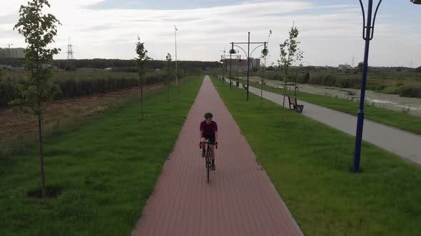 Thumbnail for Woman is cycling on road aero bike on cycle path, drone view.
