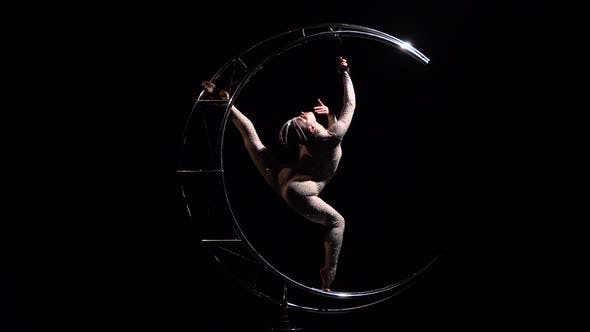 Thumbnail for Acrobat Rotates on a Metal Structure in a Vertical String. Black Background