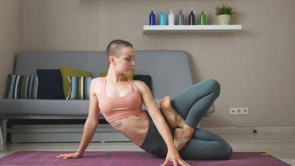 Young Healthy Caucasian Woman Practicing Yoga on the Mat in the White Large Room.
