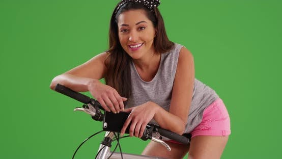 Thumbnail for Trendy Latina female resting on bicycle, smiling at camera on green screen