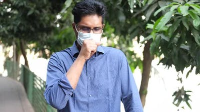 Young Asian Man in Face Mask Coughing and Sneezes Outdoor