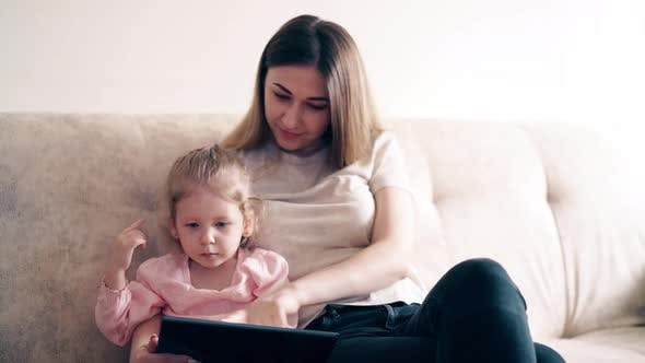 Thumbnail for : Young Cute Mother and Little Girl Are Sitting on the Couch and Teaching Using a Tablet Computer