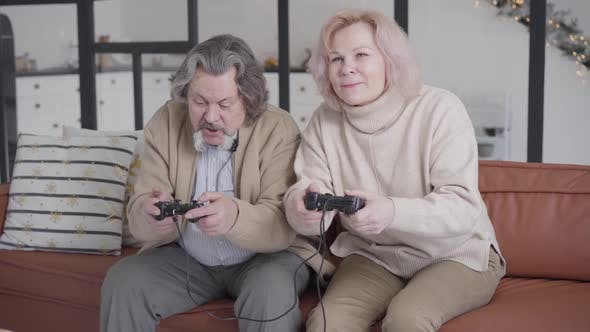 Thumbnail for Cheerful Absorbed Senior Man and Woman Playing Video Games with Game Consoles, Portrait of Joyful