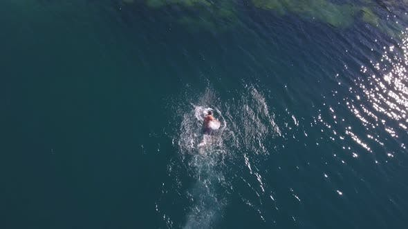 Aerial view. A muscular man swims quickly in the crystal clear sea water. Top view. Summer vacation