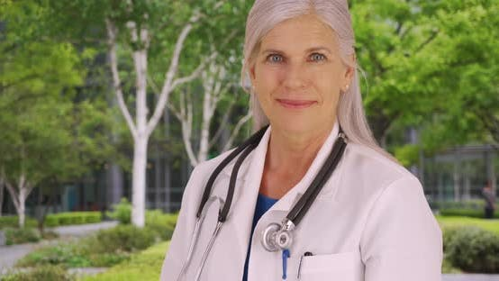 Thumbnail for Smiling portrait of mature woman doctor on hospital grounds