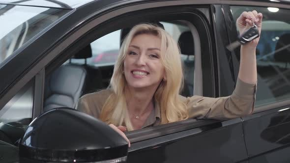 Thumbnail for Happy Caucasian Woman with Blond Hair Sitting in Salon and Bragging Car Keys