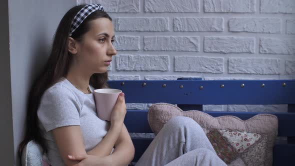 Sad Woman Sitting on Couch with Cup