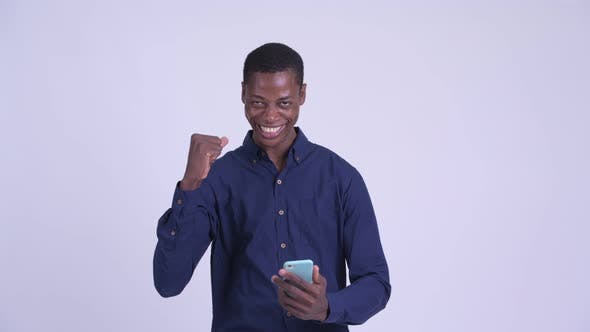 Cover Image for Young Happy African Businessman Using Phone and Getting Good News