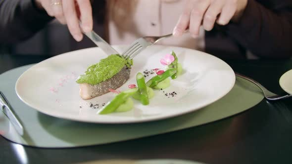 Thumbnail for Business Woman Cutting Fish with Knife and Fork at Restaurant