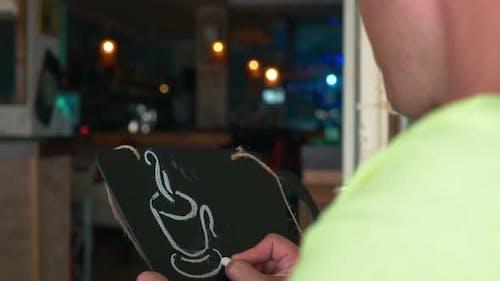 Mann zeichnet eine Kreide auf einem schwarzen Brett