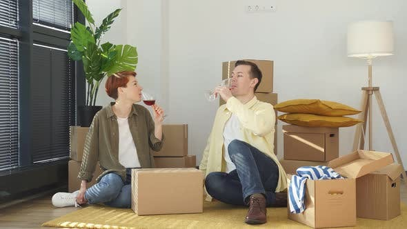 Beautiful Senior Romantic Couple in Love Sitting on Apartment Floor with Boxes Around Celebrating