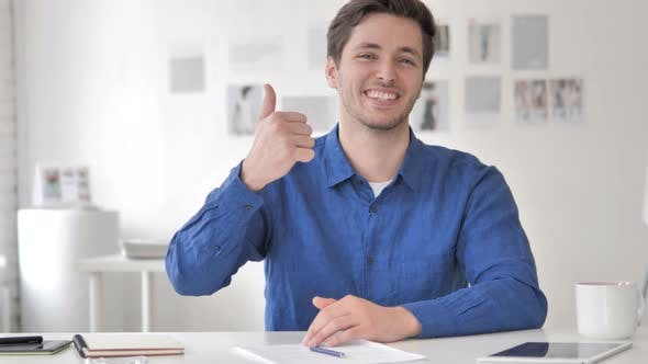 Thumbnail for Thumbs Up by Casual Adult Man Sitting at Workplace