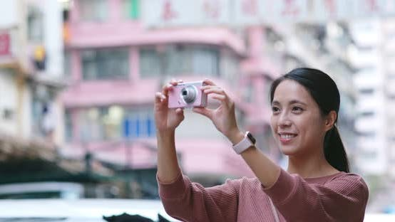 Thumbnail for Woman travel in Hong Kong, take photo on camera in the street