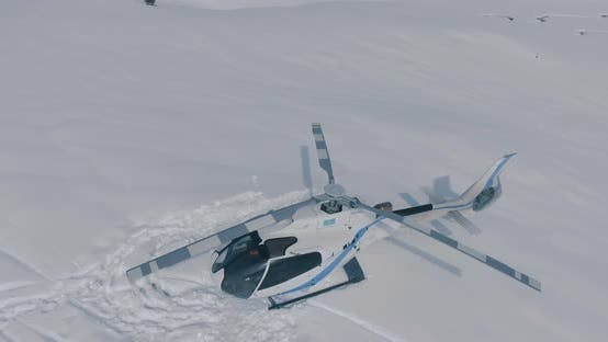 Thumbnail for Aerial view a parked white rescue helicopter standing in the snow in the winter mountains