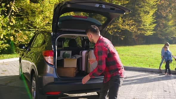 Thumbnail for Attractive Young Bearded Man Unloading From the Trunk Green Plants, Boxes