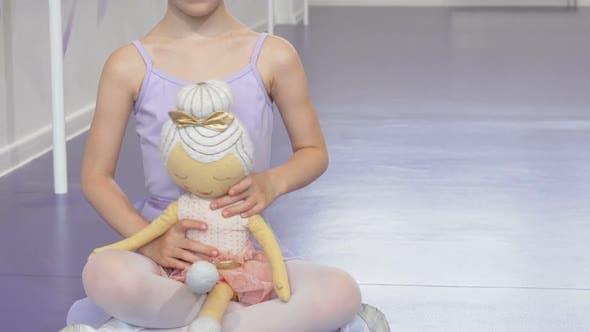 Thumbnail for Cute Happy Little Ballerina Girl Smiling Joyfully Holding Ballerina Doll