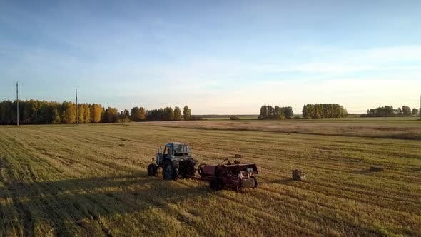 Tractor with Rectangular Baler Make Shadows on Field