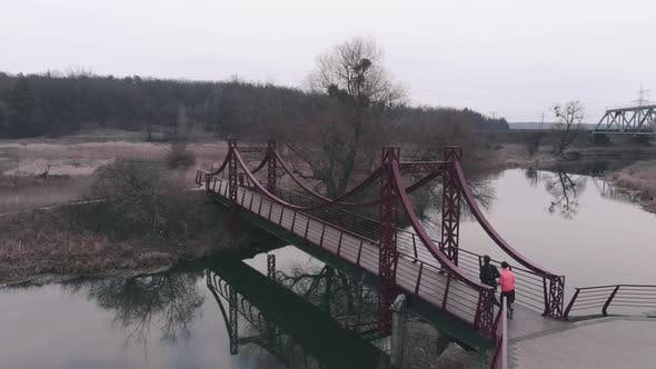 Thumbnail for Sportive couple running on bridge, Man and woman jogging in park with river and bridge