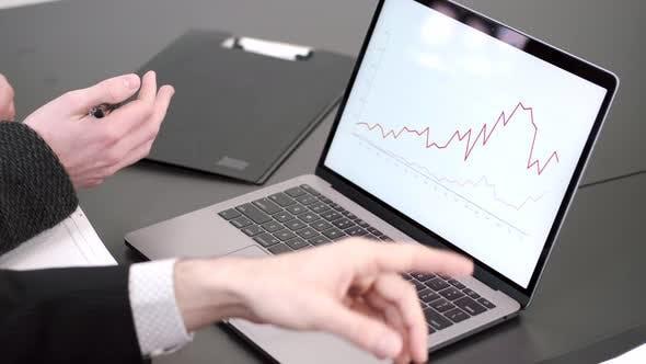 Finger der Männer zeigen auf den Laptop-Bildschirm auf den Schreibtisch